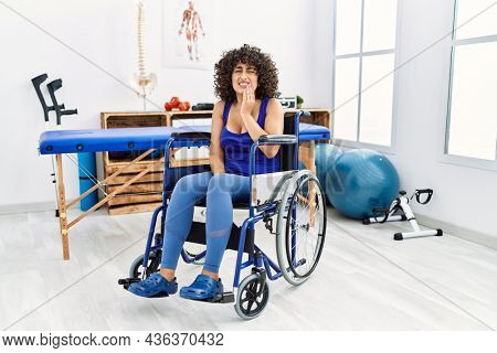 Young middle eastern woman sitting on wheelchair at physiotherapy clinic touching mouth with hand with painful expression because of toothache or dental illness on teeth. dentist