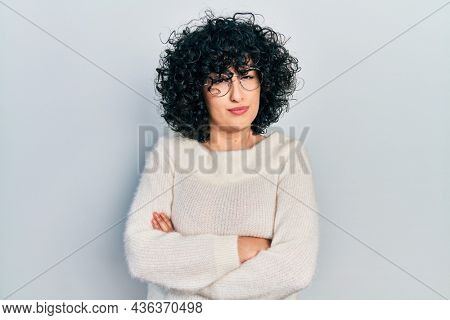 Young middle east woman with arms crossed gesture skeptic and nervous, frowning upset because of problem. negative person.