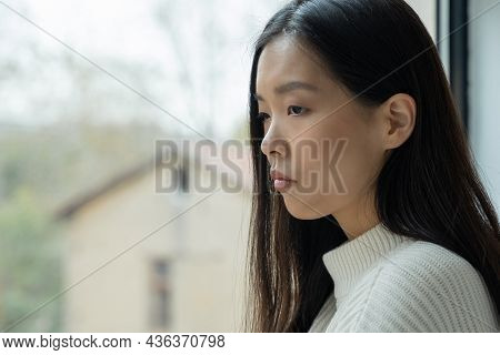 A Young Disappointed Asian Woman Is Sitting In The House And Looking Out The Window.