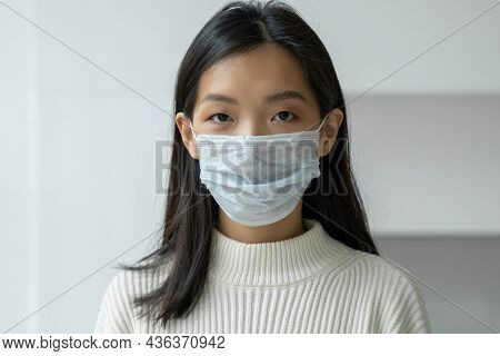 Young Asian Woman In A Protective Medical Mask To Protect Against Viral Diseases Looks Into The Came