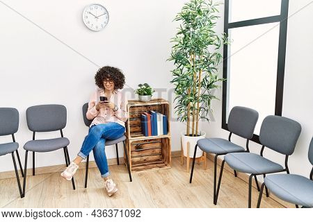 Young middle east woman using smartphone sitting on chair at waiting room