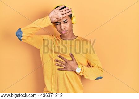 Young african american guy listening to music using headphones touching forehead for illness and fever, flu and cold, virus sick