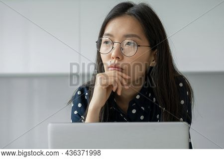 A Thoughtful Asian Businesswoman With Glasses Working With A Laptop Looks Into The Distance. The Stu