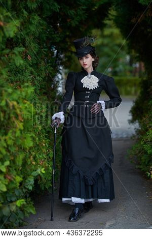 Historical reconstruction of the late 19th and early 20th century. An elegant dark-haired lady in a strict black dress and hat walks through the park. Historical makeup and hairstyle.