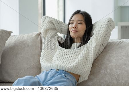 Beautiful Young Asian Woman, In A Sweatshirt, Resting On The Sofa In The Living Room, Throws Her Han