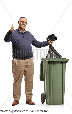Mature man throwing a plastic bag in a dustbin and gesturing a thumb up sign isolated on white background