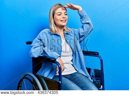 Beautiful caucasian woman sitting on wheelchair very happy and smiling looking far away with hand over head. searching concept.