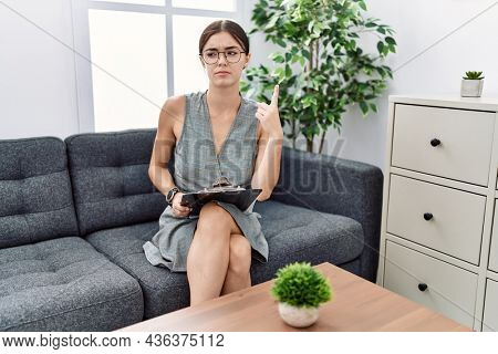 Young hispanic woman working at psychology clinic pointing up looking sad and upset, indicating direction with fingers, unhappy and depressed.