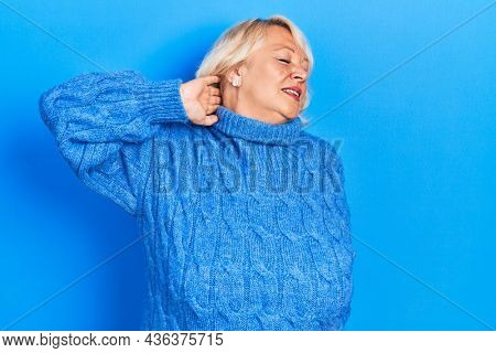 Middle age blonde woman wearing casual clothes suffering of neck ache injury, touching neck with hand, muscular pain