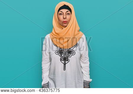 Middle age hispanic woman wearing traditional islamic hijab scarf with serious expression on face. simple and natural looking at the camera.