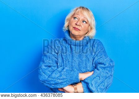Middle age blonde woman wearing casual clothes looking to the side with arms crossed convinced and confident