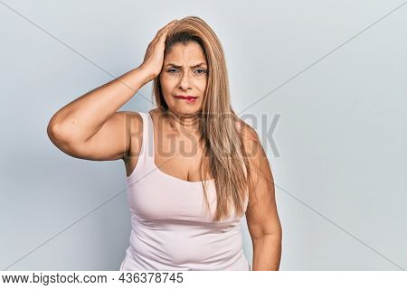 Middle age hispanic woman wearing casual style with sleeveless shirt confuse and wonder about question. uncertain with doubt, thinking with hand on head. pensive concept.