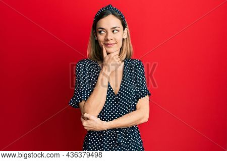 Young caucasian blonde woman wearing beautiful black and white dress with hand on chin thinking about question, pensive expression. smiling with thoughtful face. doubt concept.