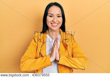 Beautiful hispanic woman with nose piercing wearing yellow leather jacket praying with hands together asking for forgiveness smiling confident.