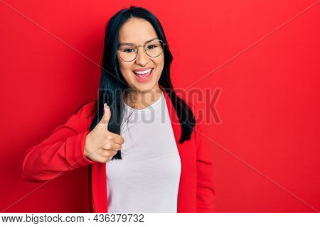 Beautiful hispanic woman with nose piercing wearing casual look and glasses doing happy thumbs up gesture with hand. approving expression looking at the camera showing success.