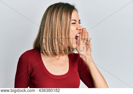 Young caucasian blonde woman wearing casual jumper shouting and screaming loud to side with hand on mouth. communication concept.