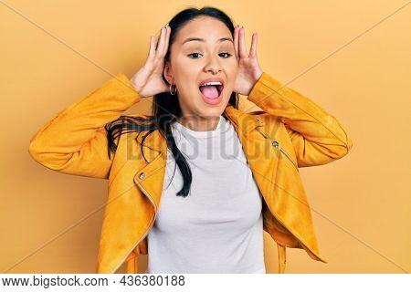 Beautiful hispanic woman with nose piercing wearing yellow leather jacket smiling cheerful playing peek a boo with hands showing face. surprised and exited