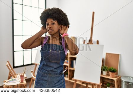 Young african american woman with afro hair at art studio trying to hear both hands on ear gesture, curious for gossip. hearing problem, deaf