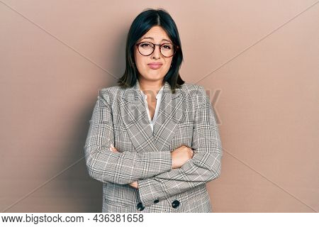 Young hispanic woman with arms crossed gesture clueless and confused expression. doubt concept.