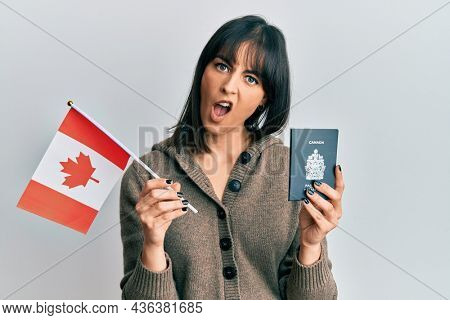 Young hispanic woman holding canada flag and passport in shock face, looking skeptical and sarcastic, surprised with open mouth