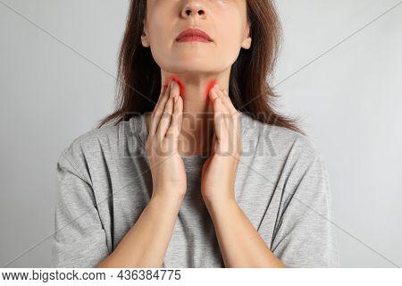 Mature Woman Doing Thyroid Self Examination On Light Background, Closeup