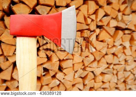 An Axe On The Background Of A Woodpile Of Wood Chopped For Burning In The Oven.preparation For Winte