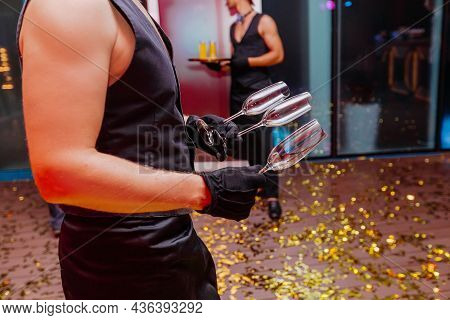 Handsome Waiter Holding In Naked Hands Empty Glasses For Champagne. Night Party Celebration In Club