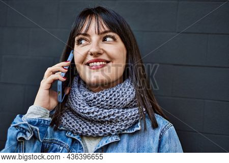 Young brunette woman smiling happy speaking on the phone leaning on the wall