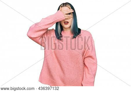 Young modern girl wearing pink wool winter sweater peeking in shock covering face and eyes with hand, looking through fingers with embarrassed expression.