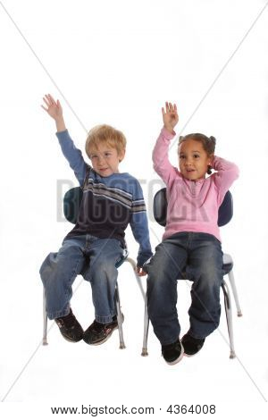 Two Kids Raising Their Hands In School