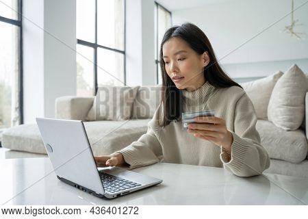 A Young Asian Woman Holding A Credit Card And Using A Laptop. A Female Entrepreneur Working From Hom
