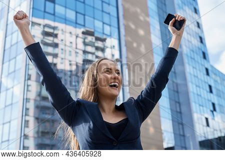 Excited European Business Woman Got Promotion, Successfully Completed Project, Raises Hands In Victo