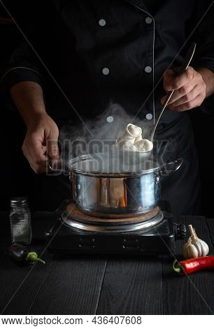 Chef Cooks Meat Dumplings In A Saucepan In The Restaurant Kitchen. Close-up Of Hands Of The Cook Dur