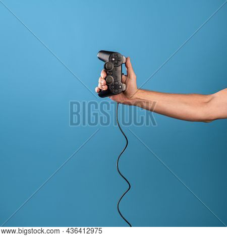 Play Computer Games , Become A Professional Gamer. A Mans Hand Holds A Gamepad With A Wire, A Photo