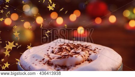 Image of stars flying over christmas hot chocolate drink and candles. christmas christmas, tradition and celebration concept digitally generated image.