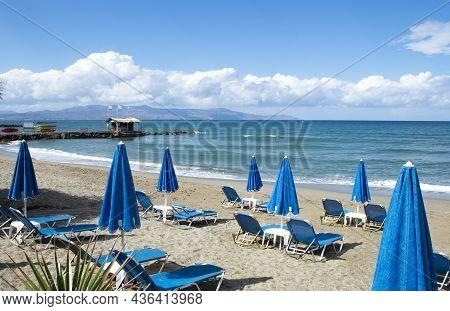 Crete Island, Greece Agia Marina Beach Near Chania Parasols And Sun Loungers On The Sands