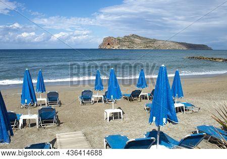 Crete Island, Greece Agia Marina Beach Near Chania Parasols And Sun Loungers On The Sands Rocky Outc