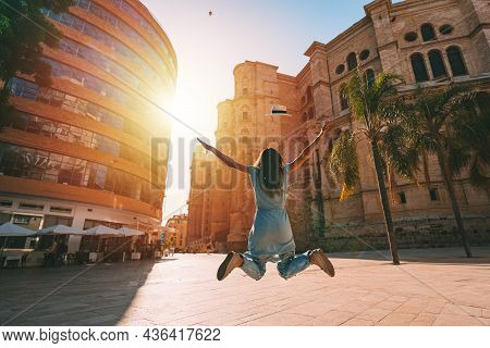 Happy Carefree Woman Jumping And Enjoying Life On Summer Vacation In Spain. Tourist Woman With Sun H