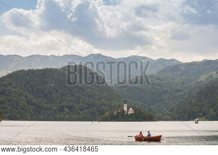 Bled, Slovenia - June 12, 2021: Tourists On A Rowing Boat In Front Of Blejsko Ostrvo, Bled Island, O