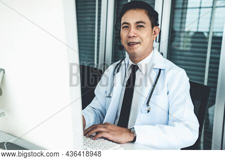 Doctor Wearing Headset Talking Actively On Video Call In A Clinic Or Hospital . Concept Of Telehealt