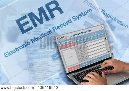 Someone Working On Electronic Medical Record With Blue Background Of Medical Record Screen.
