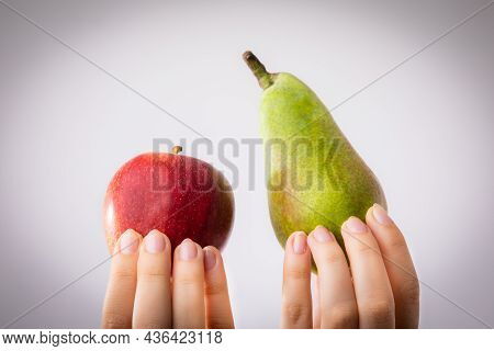 Red And Green Apple And Pear Held In Female Hands. Conceptual For Comparison, Differentiation And Ch