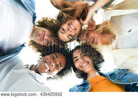 Multi-ethnic Group Of Friends With Their Heads Together In A Circle.