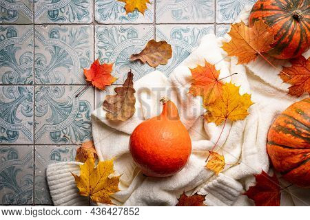 Cozy Autumn Flat Lay With Pumpkins, Knitted Woolen Sweater And Autumn Leaves Candle On Tile Backgrou