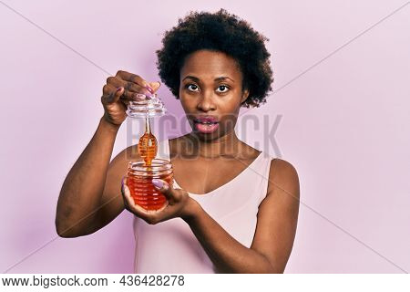 Young african american woman holding honey in shock face, looking skeptical and sarcastic, surprised with open mouth