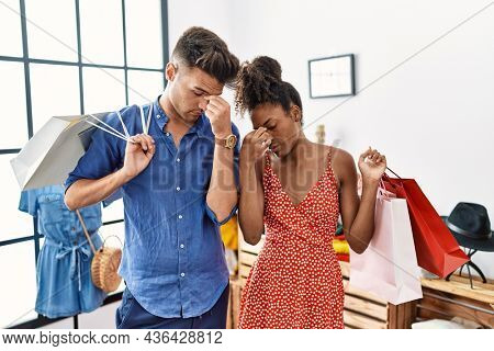 Young interracial couple holding shopping bags at retail shop tired rubbing nose and eyes feeling fatigue and headache. stress and frustration concept.