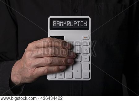Banruptcy Word On Calculator In Hand Over Black Background.