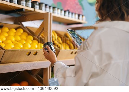 Close-up Side View Of Unrecognizable Young Woman Choosing Products In Market Walking Along Counters