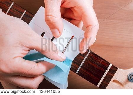 Guitar Master Polishing Frets Of Electric Guitar With Template On Wooden Table Top With Guitar Care