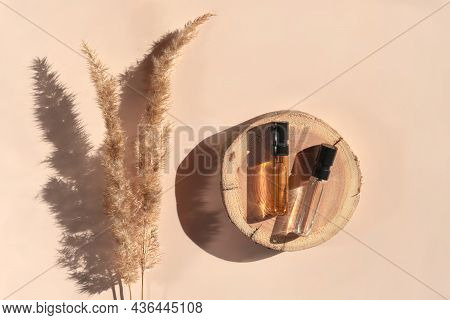 Two Glass Perfume Samples On A Wooden Tray Lying On A Beige Background With Pampas Grass. Luxury And